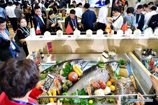 Visitors take photos of foods at the Food & Agricultural Products area during the first China International Import Expo (CIIE) in Shanghai, east China, Nov. 6, 2018. Various foods from all over the world are exhibited in the CIIE. (Xinhua/Li Xin)