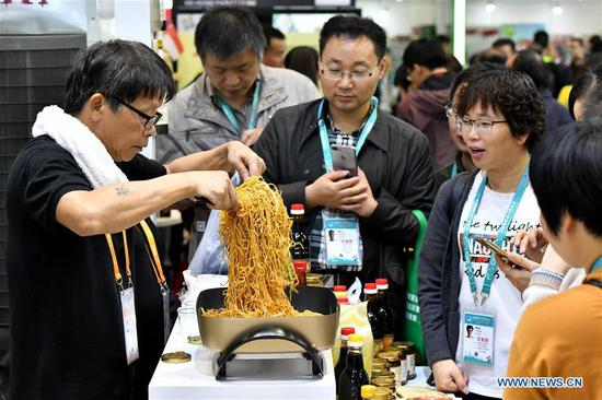 A staff member of a Singaporean seasoning company make chow mein during the first China International Import Expo (CIIE) in Shanghai, east China, Nov. 7, 2018. Various foods from all over the world are exhibited in the CIIE. (Xinhua/Li Xin)