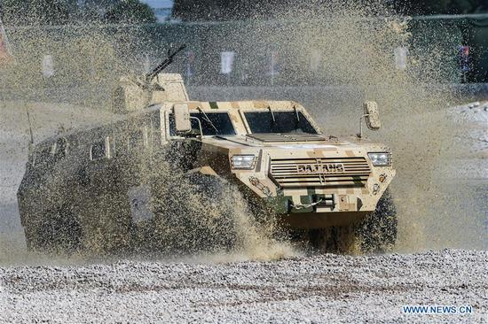 An armored vehicle wades through a puddle during a dynamic display of ground military equipments at the 12th China International Aviation and Aerospace Exhibition (Airshow China) in Zhuhai, south China's Guangdong Province, on Nov. 7, 2018. (Xinhua/Yang Guang)
