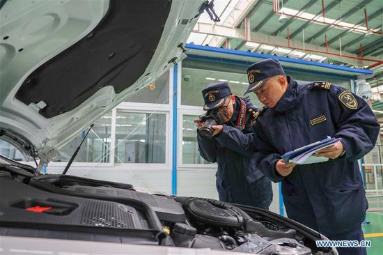 Customs staff members check a Mercedes-Benz car unloaded from a carriage of a new China-Europe freight train carrying commercial vehicles, the first of its kind, in Chongqing, southwest China, Nov. 19, 2018. The customs clearance process of those commercial vehicles was finished on Monday. The train, carrying 112 Mercedes-Benz cars, started its trip in Bremen, Germany on Oct. 29, and traveled 14,000 km across Germany, Poland, Lithuania, Belarus, Russia, and Kazakhstan, and arrived in Chongqing via the Horgos Port, Xinjiang Uygur Autonomous Region. The one-way trip took 16 days and 16 hours, reducing transportation time by more than two-thirds compared with by sea. Compared with shipping containers, train carriages are larger and less restricted by seasonal changes. (Xinhua/Liu Chan)
