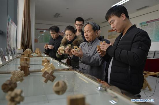 Hou Quanchen introduces Kong Ming Locks to the visitors in Shahe City, north China's Hebei Province on Nov. 28, 2018. Hou Quanchen, who is in his seventies, has devoted himself in the studying and making of Kong Ming Locks and has tried to promote this art among local residents ever since his retirement. (Xinhua/Tian Xiaoli)
