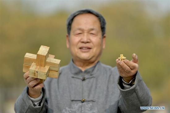 Hou Quanchen shows his self-made Kong Ming Locks in Shahe City, north China's Hebei Province on Nov. 28, 2018. Hou Quanchen, who is in his seventies, has devoted himself in the studying and making of Kong Ming Locks and has tried to promote this art among local residents ever since his retirement. (Xinhua/Tian Xiaoli)