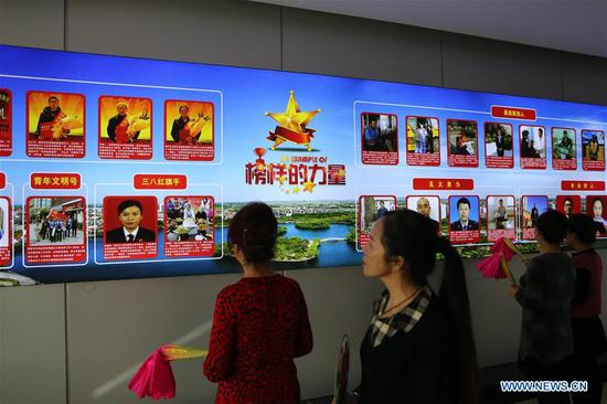 People watch posters at a culture promotion center in Laixi, east China's Shandong Province, Nov. 29, 2018. (Xinhua/Ding Hongfa)