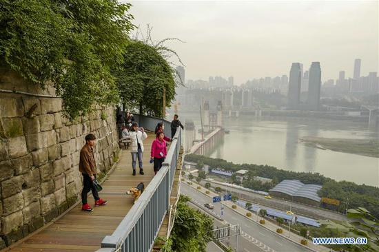 Visitors walk on the plank road along the 3rd footpath in Yuzhong district of Chongqing, southwest China, Dec. 2, 2018. Since 2016, local authority has rolled out plans to renovate 14 footpaths with a total length of 39.5 kilometers. The 14 footpaths linking Chongqing's natural and cultural highlights provide visitors the city's most beautiful and important sights. (Xinhua/Liu Chan)