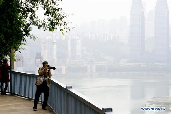 A man takes photos on the plank road along the 3rd footpath in Yuzhong district of Chongqing, southwest China, Dec. 2, 2018. Since 2016, local authority has rolled out plans to renovate 14 footpaths with a total length of 39.5 kilometers. The 14 footpaths linking Chongqing's natural and cultural highlights provide visitors the city's most beautiful and important sights. (Xinhua/Liu Chan)