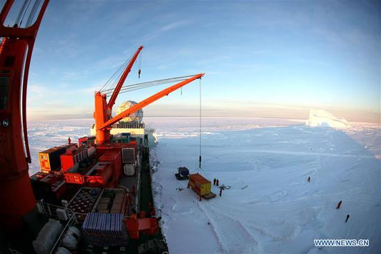 A crane unloads a container of supplies from China's research icebreaker Xuelong in Antarctica, Dec. 2, 2018. China's research icebreaker Xuelong, also known as the Snow Dragon, is now 44 kilometers away from the Zhongshan station. Unloading operations have been carried out after the routes were determined. (Xinhua/Liu Shiping)