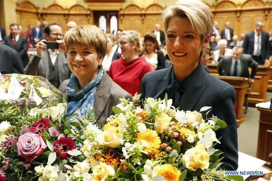 Newly-elected Federal Councilors Karin Keller-Sutter (R) and Viola Amherd pose for photos at the Federal Parliament in Bern, capital of Switzerland, Dec. 5, 2018. Switzerland's parliament Wednesday chose two women, one from a centrist party and one from a center-right party, to join the country's seven-person executive, the Federal Council, which operates as the cabinet. (Xinhua/Ruben Sprich)
