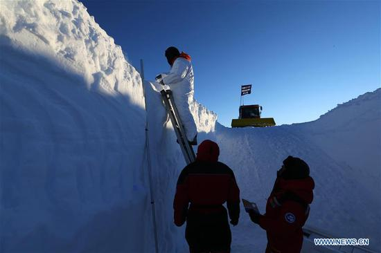 A member of China's 35th research expedition takes the sample from a snow pit in Antarctica, Dec. 20, 2018. (Xinhua/Liu Shiping)