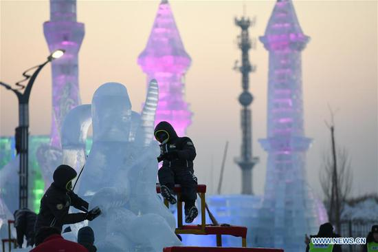 Contestants carve an ice sculpture during an international ice sculpture competition in Harbin, capital of northeast China's Heilongjiang Province, Jan. 3, 2019. (Xinhua/Wang Song)