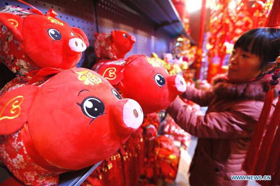 A woman selects New Year decorations at a market in Jimo District of Qingdao, east China's Shandong Province, Jan. 8, 2019. People are busy buying New Year decorations to greet the upcoming Lunar New Year, which starts from the first day of the first month of the Chinese lunar calendar, or Feb. 5 this year. (Xinhua/Liang Xiaopeng)