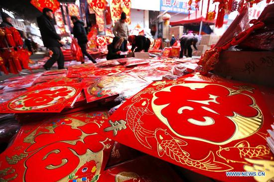 Consumers select New Year decorations at a market in Jimo District of Qingdao, east China's Shandong Province, Jan. 8, 2019. People are busy buying New Year decorations to greet the upcoming Lunar New Year, which starts from the first day of the first month of the Chinese lunar calendar, or Feb. 5 this year. (Xinhua/Liang Xiaopeng)