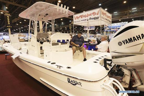 A boat salesman talks with a visitor at Houston International Boat, Sport & Travel Show in Houston, the United States, on Jan. 8, 2019. Over 1,000 boats are on display during the annual show from Jan. 4 to Jan. 13. Many retail venders use the