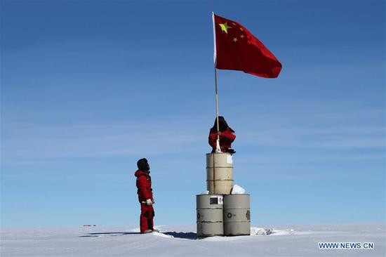 A member of China's 35th Antarctic expedition team erects the Chinese national flag at the area of the Dome Argus (Dome A), the peak of Antarctica's inland icecap, in Antarctica, Jan. 16, 2019. (Xinhua/Liu Shiping)