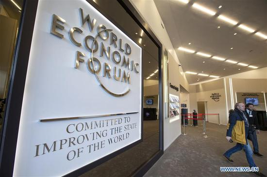 People walk by the logo of the World Economic Forum (WEF) in Davos, Switzerland, Jan. 21, 2019. The WEF Annual Meeting will kick off in Davos on Tuesday. (Xinhua/Xu Jinquan)