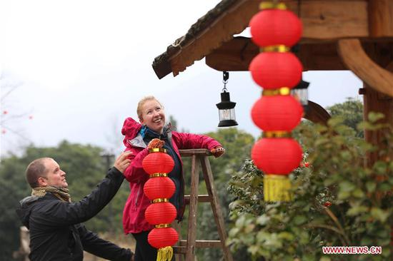 A British couple hang red lanterns for the upcoming Spring Festival at a hostel in Wulingyuan District of Zhangjiajie City, central China's Hunan Province, Jan. 31, 2019. The Spring Festival, or the Chinese Lunar New Year, falls on Feb. 5 this year. (Xinhua/Wu Yongbing)