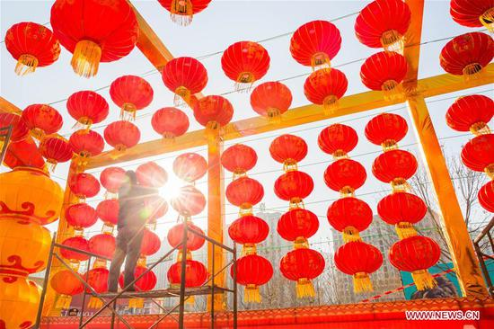 A worker hangs red lanterns for the upcoming Spring Festival at the gate of a shopping mall in Handan City, north China's Hebei Province, Feb. 1, 2019. The Spring Festival, or the Chinese Lunar New Year, falls on Feb. 5 this year. (Xinhua/Qiao Hailong)