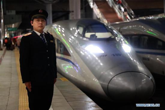 Train conductor Yin Li poses for a photo before the high-speed train G529 departs from the Beijing West Railway Station in Beijing, capital of China, Feb. 1, 2019. Bullet Train G529/530 runs over 15 hours, the longest travel time of China's high-speed railway, between China's capital Beijing and Beihai of south China's Guangxi Zhuang Autonomous Region. The railway line covers a total length of about 2,675 kilometers. Train conductor Yin Li, a 30-year-old army veteran, is strict with himself and his colleagues. He inspects the bullet train G529/530 every day to ensure travel safety. (Xinhua/Xing Guangli)