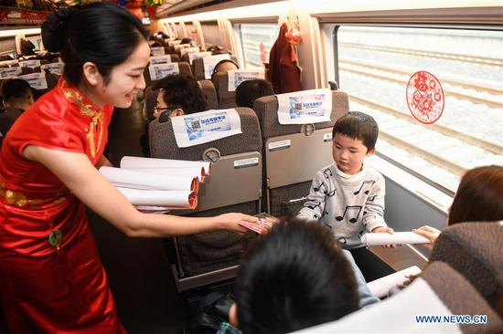 An attendant offers gifts to passengers aboard a bullet train from Hangzhou of east China's Zhejiang Province to Huangshan of east China's Anhui Province, on Feb. 2, 2019. Staff members aboard the train staged a performance Saturday to extend greetings to the passengers, ahead of the Spring Festival, or the Chinese Lunar New Year, which falls on Feb. 5 this year. (Xinhua/Huang Zongzhi)