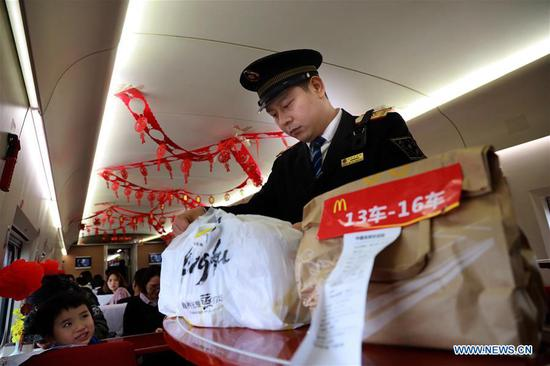 Train conductor Yin Li arranges meals passengers ordered online aboard the high-speed train G529, Feb. 1, 2019. Bullet Train G529/530 runs over 15 hours, the longest travel time of China's high-speed railway, between China's capital Beijing and Beihai of south China's Guangxi Zhuang Autonomous Region. The railway line covers a total length of about 2,675 kilometers. Train conductor Yin Li, a 30-year-old army veteran, is strict with himself and his colleagues. He inspects the bullet train G529/530 every day to ensure travel safety. (Xinhua/Xing Guangli)