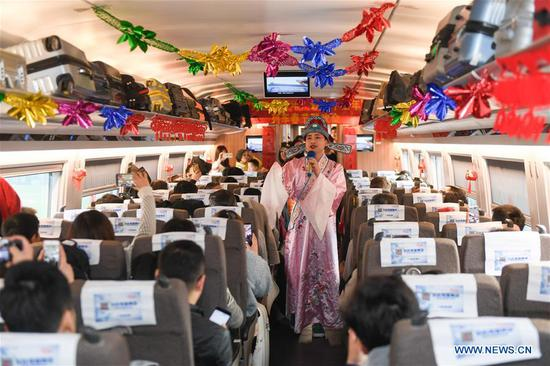 An attendant performs aboard a bullet train from Hangzhou of east China's Zhejiang Province to Huangshan of east China's Anhui Province, on Feb. 2, 2019. Staff members aboard the train staged a performance Saturday to extend greetings to the passengers, ahead of the Spring Festival, or the Chinese Lunar New Year, which falls on Feb. 5 this year. (Xinhua/Huang Zongzhi)