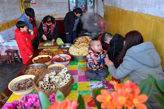 A family which was lifted out of poverty prepare food for Chinese Lunar New Year's in Hujiashe Village of Shizhuang Township in Fenyang City, north China's Shanxi Province, Feb. 3, 2019. The Spring Festival, or the Chinese Lunar New Year which falls on Feb. 5 this year, is the most important festival in China.