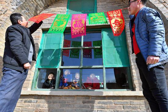 A family which was lifted out of poverty decorate house for Chinese Lunar New Year's in Hujiashe Village of Shizhuang Township in Fenyang City, north China's Shanxi Province, Feb. 3, 2019. The Spring Festival, or the Chinese Lunar New Year which falls on Feb. 5 this year, is the most important festival in China.