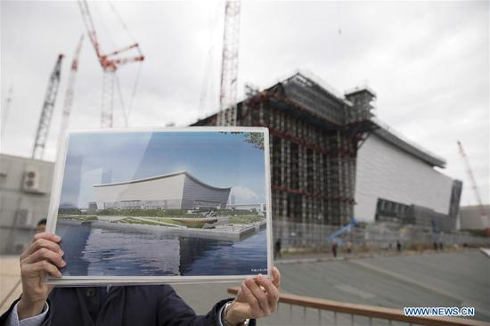 A staff member shows a design sketch of Ariake Arena, one of the Tokyo 2020 Olympic Games venues, at Ariake Arena construction site in Tokyo, Japan, on Feb. 12, 2019. This venue for volleyball games has been finished 51% construction works till the end of last month. (Xinhua/Du Xiaoyi)