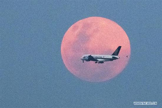 An airplane flies against the rising full moon on the eastern coast of Singapore on Feb. 19, 2019. (Xinhua/Then Chih Wey)