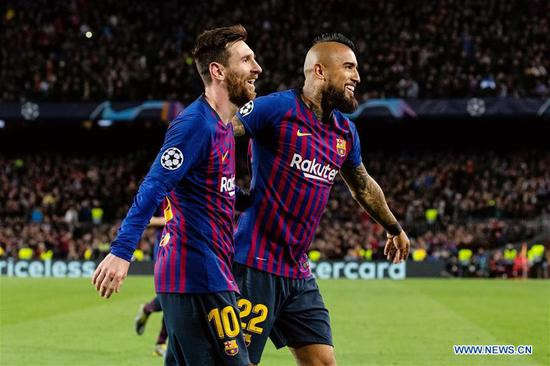Barcelona's Lionel Messi (L) and Arturo Vidal celebrate a goal by teammate Gerard Pique during the UEFA Champions League match between Spanish team FC Barcelona and French team Lyon in Barcelona, Spain, on March 13, 2019. Barcelona won 5-1 and advanced to the quarterfinals. (Xinhua/Joan Gosa)