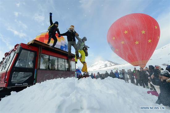 Tourists try jumping in snow at Hom Village in Burqin County, northwest China's Xinjiang Uygur Autonomous Region, Nov. 29, 2018. Xinjiang has organized various events to boost its winter tourism industry. Between November of 2018 and January of 2019, Xinjiang received more than 11 million tourists at home and abroad, an increase of over 50 percent year on year. (Xinhua/Ding Lei)