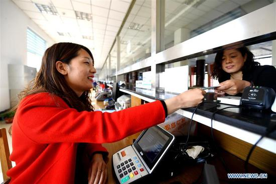 At 4:30 pm, Zhu Fang (L), a staff member of Baiyangdian scenic area, sells tickets to tourists in Xiongan New Area, north China's Hebei Province, April 1, 2019. Known as the China's