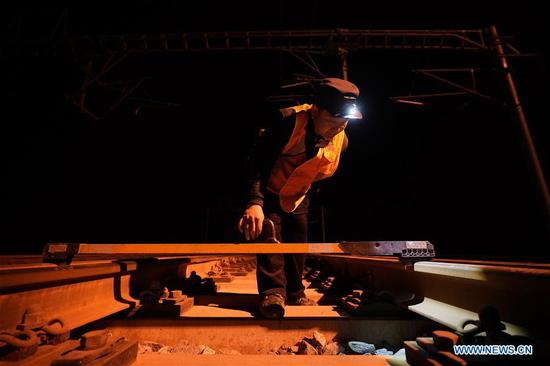 At 2:08 am, Zhang Qingkai, a railway maintainer of China Railway Beijing Group, checks the tracks of the railway line from Beijing to Xiongan in Xiongan New Area, north China's Hebei Province, April 1, 2019. Known as the China's