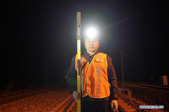 At 2:09 am, Zhang Qingkai, a railway maintainer of China Railway Beijing Group, stands on the tracks of the railway line from Beijing to Xiongan in Xiongan New Area, north China's Hebei Province, April 1, 2019. Known as the China's