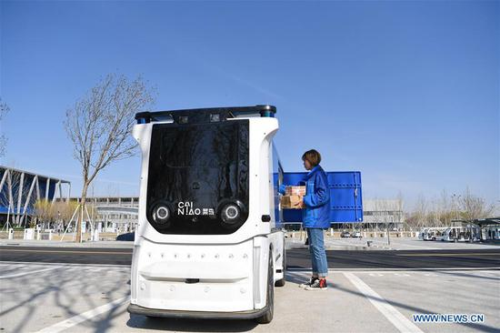 At 3:30 pm, Sun Jingyun, a staff member of Cainiao Network, loads packages into an unmanned express delivery vehicle at Xiongan citizen service center in Xiongan New Area, north China's Hebei Province, April 1, 2019. The unmanned express delivery vehicle, independently researched and developed by the Alibaba's logistics arm, was recently put into service at Xiongan citizen service center. Known as the China's