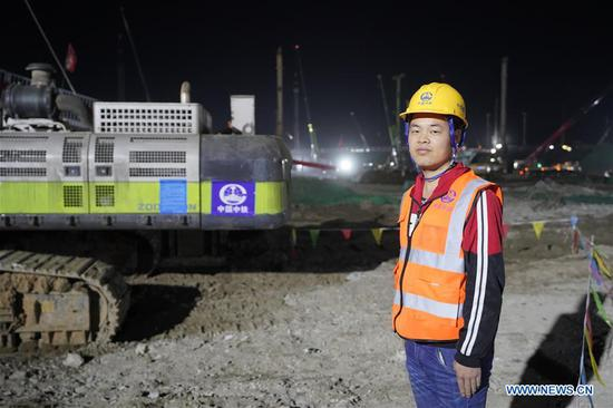 At 4:15 am, Zhang Jie, a pile machine driver of China Railway Construction Engineering Group, stands at the construction site of Xiongan Railway Station in Xiongan New Area, north China's Hebei Province, April 1, 2019. Known as the China's