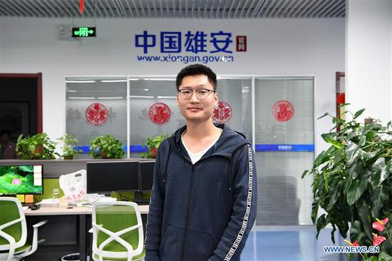 At 9 pm, Li Xin, a cameraman of the official website of Xiongan New Area, stands in the newsroom in Xiongan New Area, north China's Hebei Province, April 1, 2019. Known as the China's
