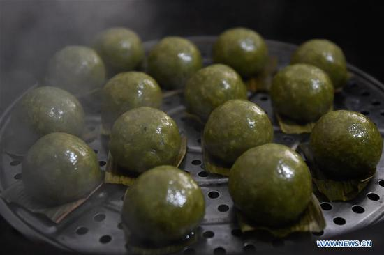 Photo taken on April 4, 2019 shows the steamed Qingtuan, or green sticky rice balls, in Yiyanshan Village of Huzhou, east China's Zhejiang Province. Qingtuan, made from glutinous rice mixed with wormwood juice and stuffed with bamboo shoot, tofu and preserved meat, is a traditional snack popular mailnly among people living in the south of Yangtze River during the Qingming Festival also known as Tomb Sweeping Day. (Xinhua/Huang Zongzhi)