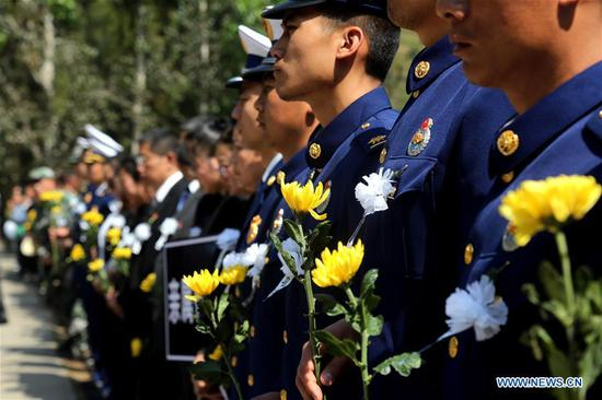 People attend a burial ceremony for the bone ashes of fireman Zhang Hao, who died while fighting a forest fire in Muli, Sichuan Province, at a martyrs' cemetery in Xichang of Liangshan Yi Autonomous Prefecture in southwest China's Sichuan Province, April 6, 2019. (Xinhua/Li Jieyi)