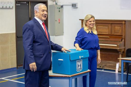 Israeli Prime Minister Benjamin Netanyahu (L) casts his ballot at a polling station in Jerusalem, April 9, 2019. Israel on Tuesday morning started day-long general elections across the country to choose its next parliament and decide the premiership. (Xinhua/JINI/Emil Salman)