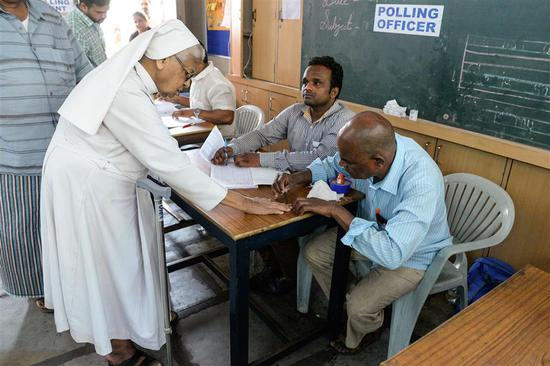 A polling officer marks the finger of a Catholic nun before voting in a booth at a polling station during India's general election in Hyderabad on April 11, 2019.