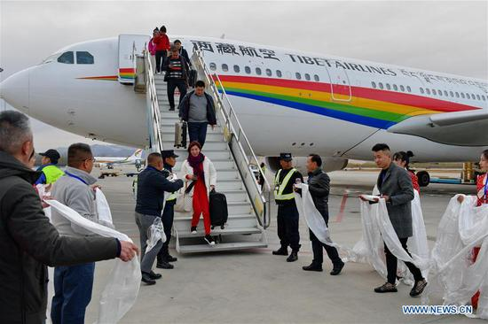 Representatives from Tibet's tourism development department and Tibet Airlines greet passengers onboard the first inbound flight from Jinan to Lhasa with hada, traditional Tibetan ceremonial scarf, at Gonggar Airport in Lhasa, capital of southwest China's Tibet Autonomous Region, April 9, 2019. Tibet Airlines launched a new air route connecting Lhasa, the autonomous region's capital, with Helsinki, by way of the city of Jinan in east China's Shandong Province. (Xinhua/Zhang Rufeng)