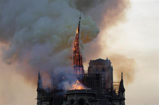 The steeple engulfed in flames collapses as the roof of the Notre-Dame de Paris Cathedral burns on April 15, 2019 in Paris.