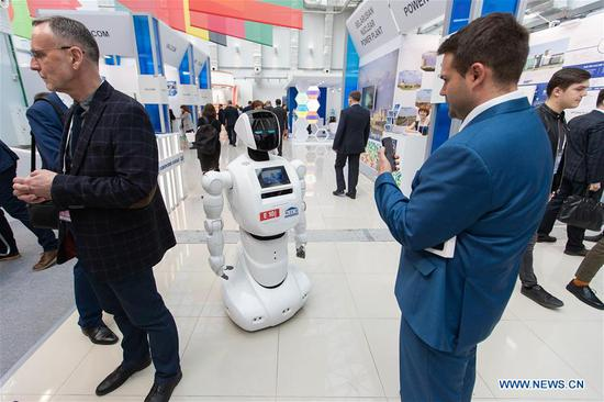 A man interacts with a robot during the 11th ATOMEXPO in Sochi, Russia, on April 15, 2019. Global experts called for the further development of nuclear technology and cooperation so as to cope with climate change and realize sustainable development at the 11th ATOMEXPO International Forum here on Monday. (Xinhua/Bai Xueqi)