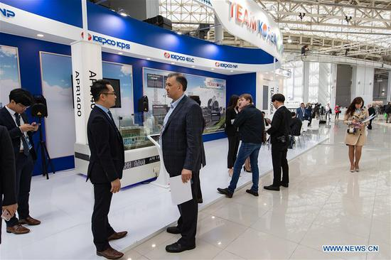 People walk past KEPCO KPS booth during the 11th ATOMEXPO in Sochi, Russia, on April 15, 2019. Global experts called for the further development of nuclear technology and cooperation so as to cope with climate change and realize sustainable development at the 11th ATOMEXPO International Forum here on Monday. (Xinhua/Bai Xueqi)