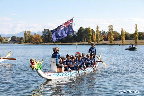 People attend the opening ceremony of the annual Australian Dragon Boat Championships in Canberra, Australia, April 17, 2019. The 22nd annual Australian Dragon Boat Championships (AusChamps) opened on Canberra's Burley Griffin Lake after the traditional eye-dotting and blessing of the boats ceremony on Wednesday. This year's event is held from April 17 to 22, and has attracted nearly 3,000 competitors from clubs throughout the country to participate in club vs club and State vs State races. (Xinhua/Chu Chen)