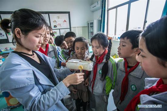 A teacher and students produce craftwork out of recycled materials during an environmental awareness activity marking Earth Day, which falls on April 22, at the Second Primary School in Donglin Township of Huzhou, east China's Zhejiang Province, April 19, 2019. (Xinhua/Xu Yu)