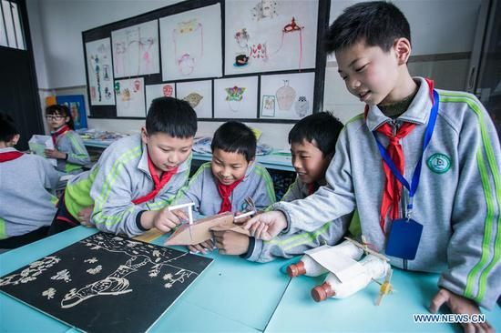 Students produce craftwork out of recycled materials during an environmental awareness activity marking Earth Day, which falls on April 22, at the Second Primary School in Donglin Township of Huzhou, east China's Zhejiang Province, April 19, 2019. (Xinhua/Xu Yu)