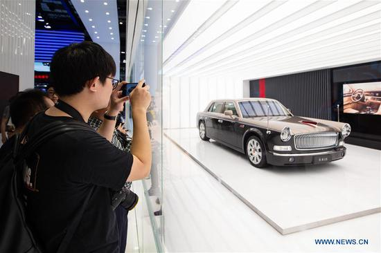 Visitors take photos of a Hongqi car displayed at the 18th Shanghai International Automobile Industry Exhibition in Shanghai, east China, April 20, 2019. (Xinhua/Su Yang)