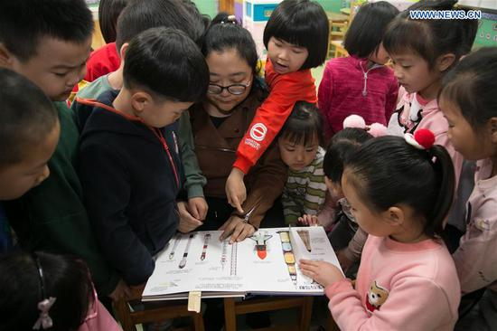 A teacher of the affiliated kindergarten of Miaofengshan ethnic school teaches children space knowledge in Mentougou District of Beijing, capital of China, April 24, 2019. Since 2016, China has set April 24 as the country's Space Day. The various activities on Space Day have become a window for the Chinese public and the world to get a better understanding of China's aerospace progress. (Xinhua/Hou Jiqing)