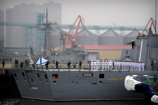 Russian sailors stand on the deck of the Russian frigate Admiral Gorshkov as it docks at a port in Qingdao in eastern China's Shandong Province. on April 21, 2019.